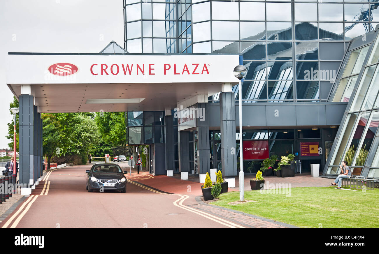 A car under the canopy in front of the Main entrance to the Crown Plaza hotel in the Finnieston area of Glasgow. - Stock Image