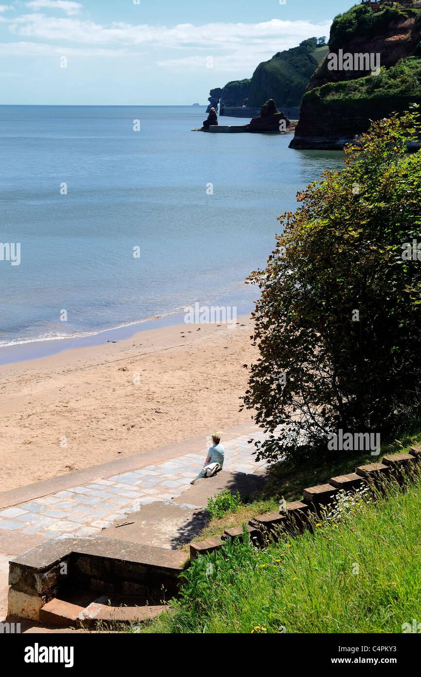 female sitting corytons cove dawlish devon england uk - Stock Image