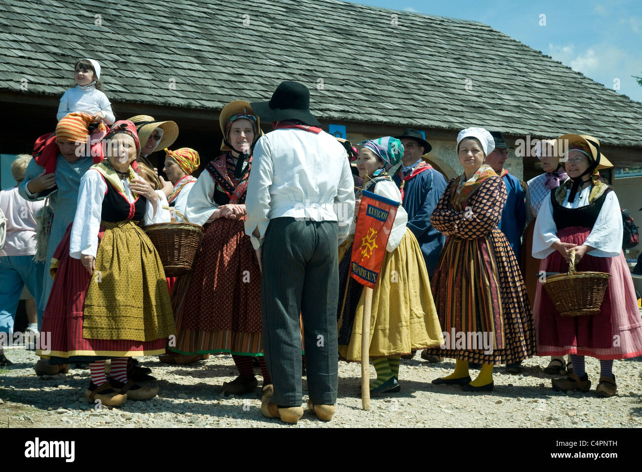 A Lozère folk group in 18th-century bonnets, full skirts and clogs, entertains the crowd at a rural hilltop - Stock Image