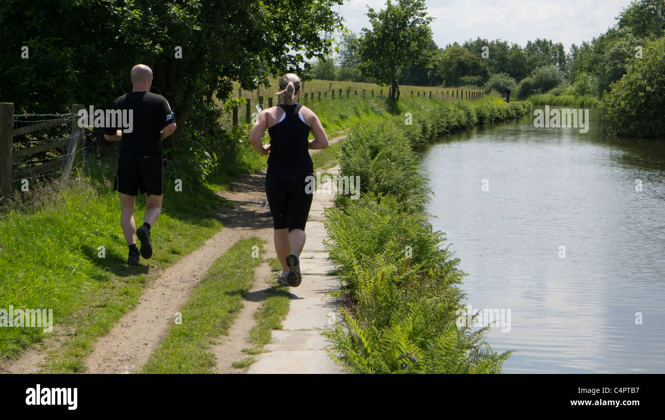 Joggers on Rochdale Canal towpath - Stock Image