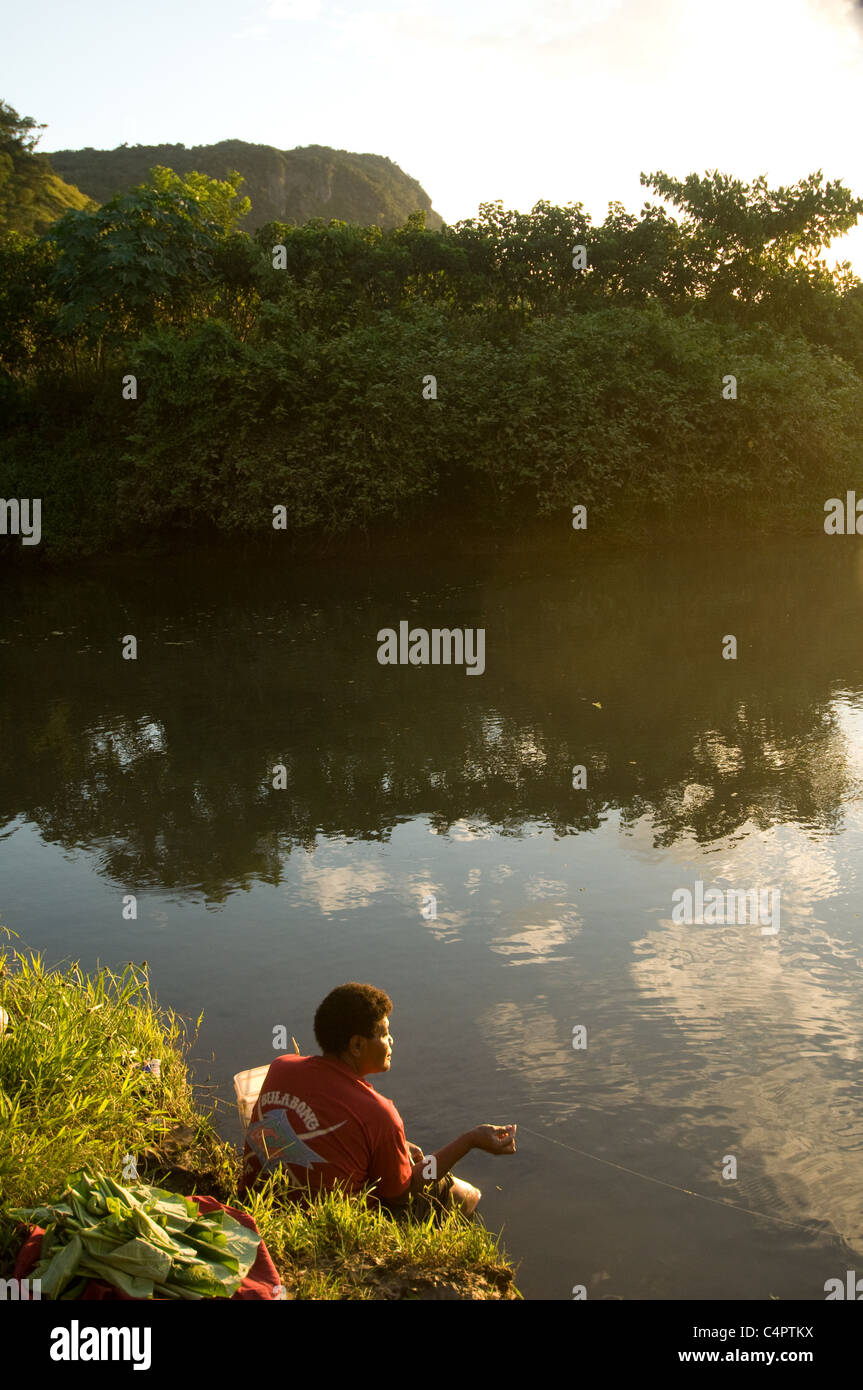 Fijian woman sits at river bank fishing in late afternoon near her village Viti Levu island Fiji South Pacific - Stock Image