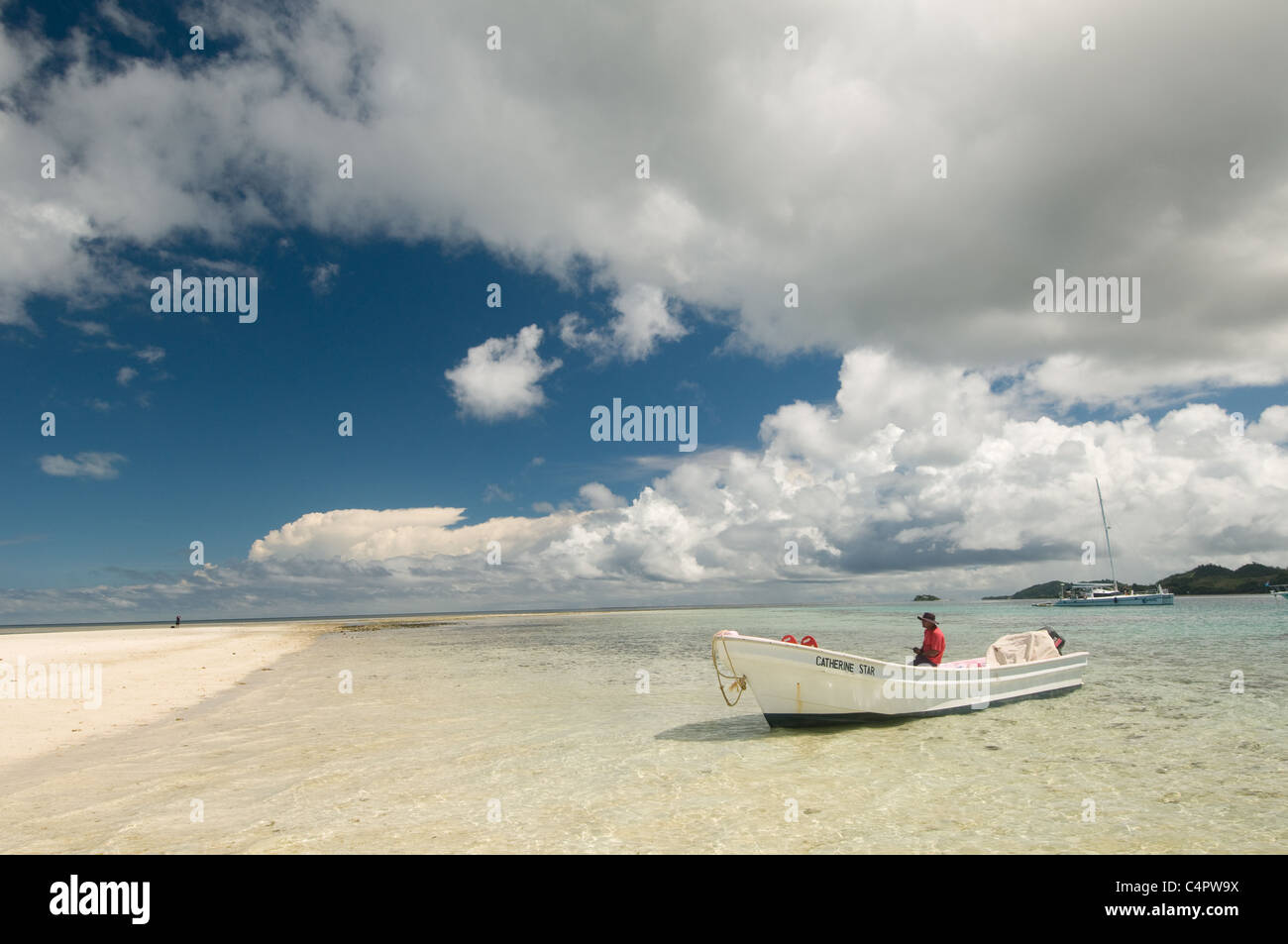 Dramatic clouds above boat on sandy beach in Mamanuca Islands of Fiji Melanesia South Pacific - Stock Image