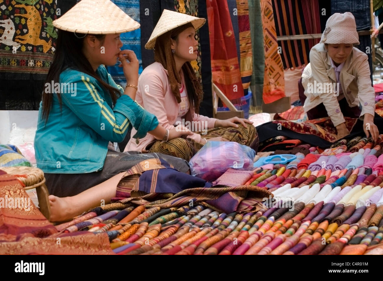 Asian women are selling colorful cloth goods at a street market in Luang Prabang, Laos. - Stock Image