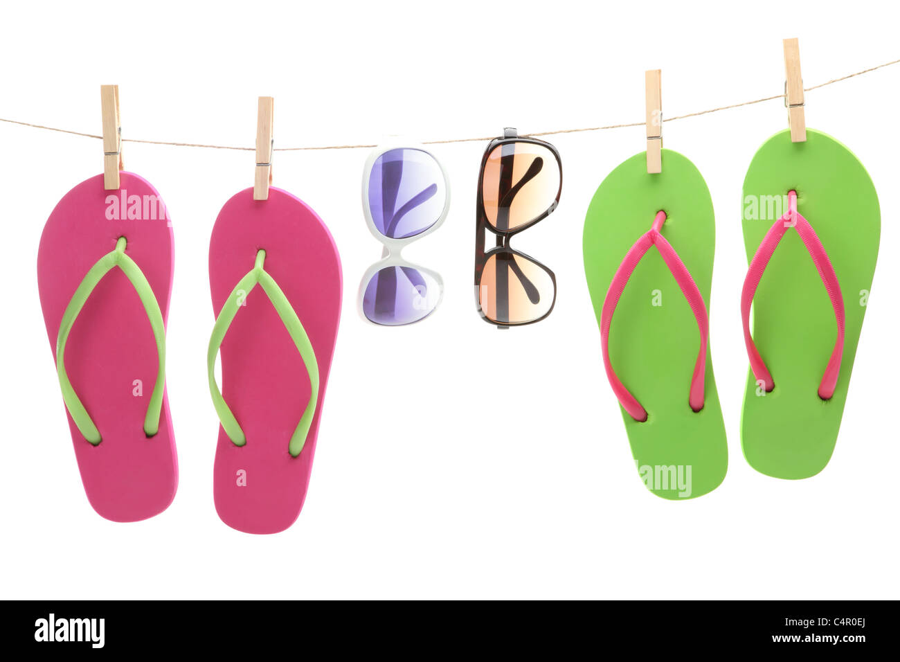 Flip-flop sandles and sunglasses hanging by clips from a clothes line - Stock Image