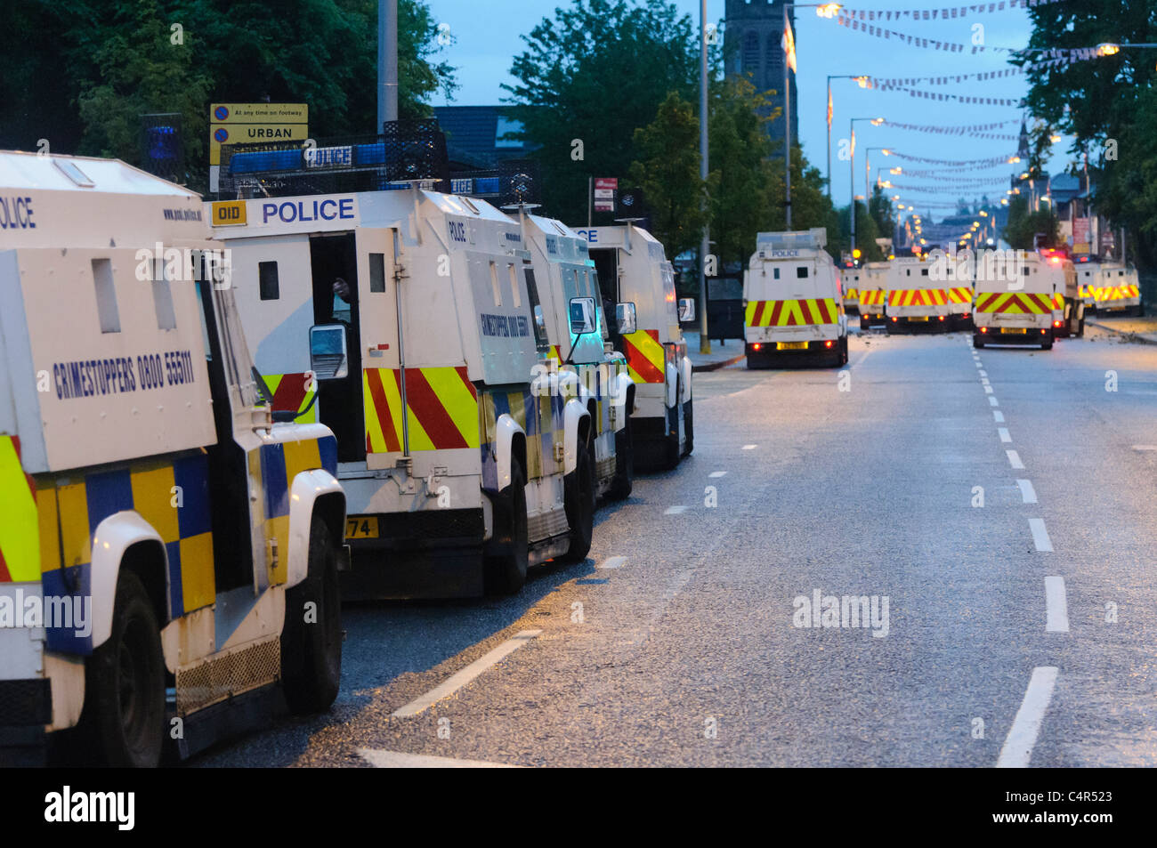 Dozens of PSNI armoured Landrovers are used to control a mob of rioters  BELFAST 21/06/2011 - Stock Image