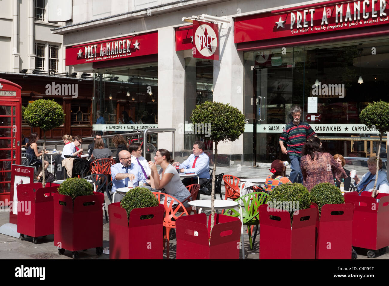 People sitting and enjoying a drink outside a Pret A Manger, St Martin's Place, London - Stock Image
