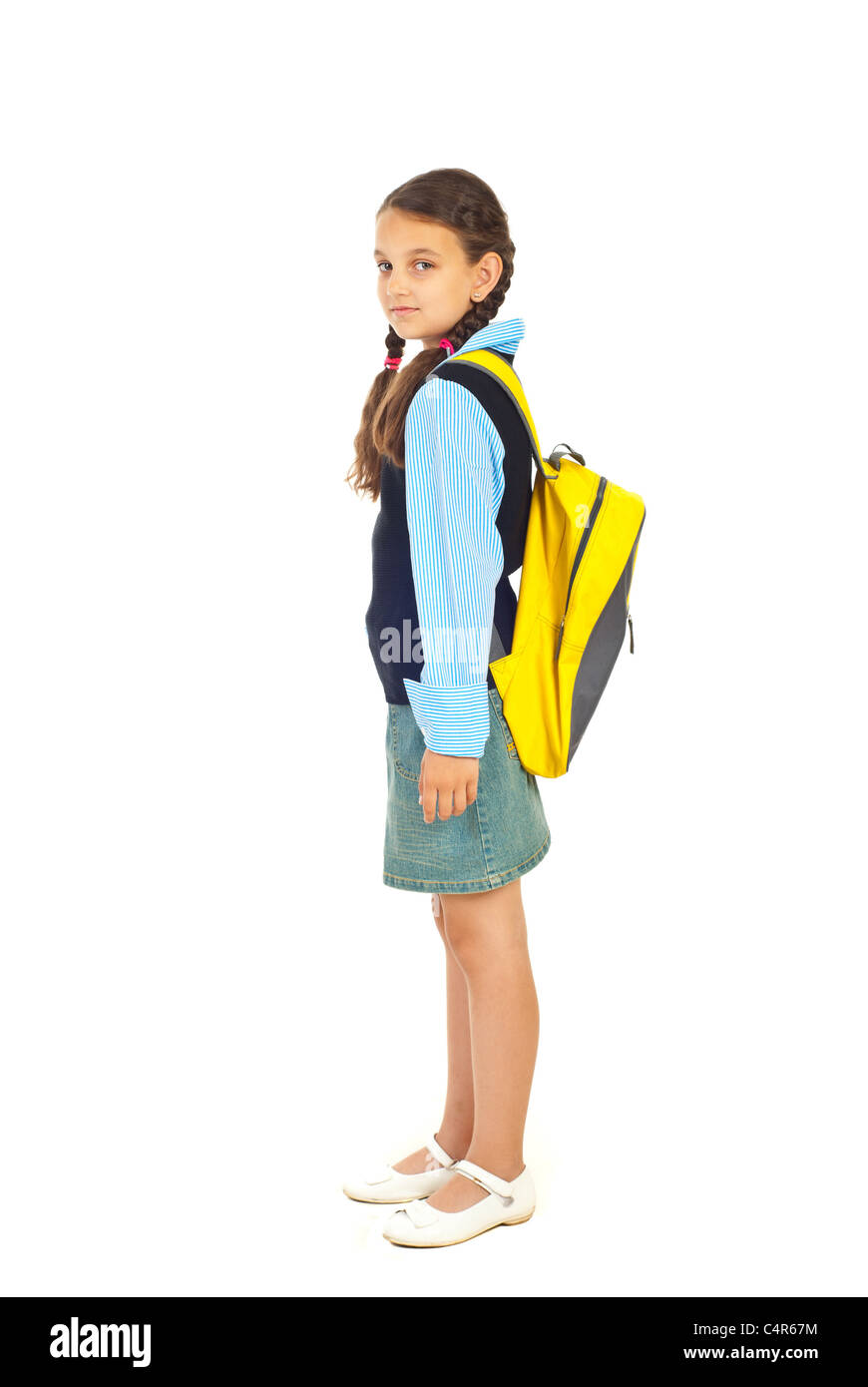 Full length of student girl standing in semi profile and looking at camera isolated on white background - Stock Image