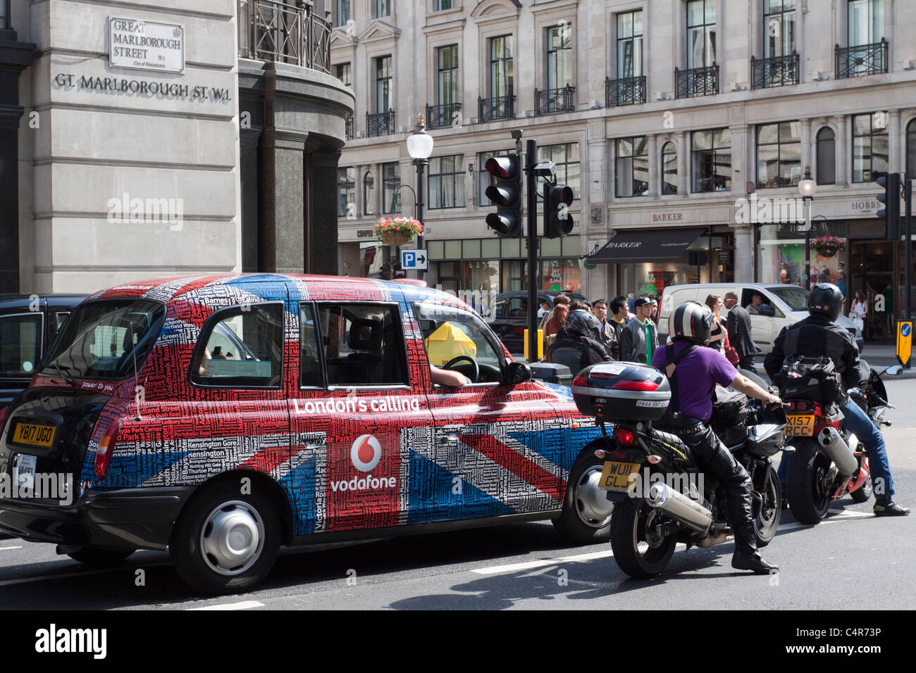 London taxi cab and motorcycles on Great Marlborough Street, London, England - Stock Image