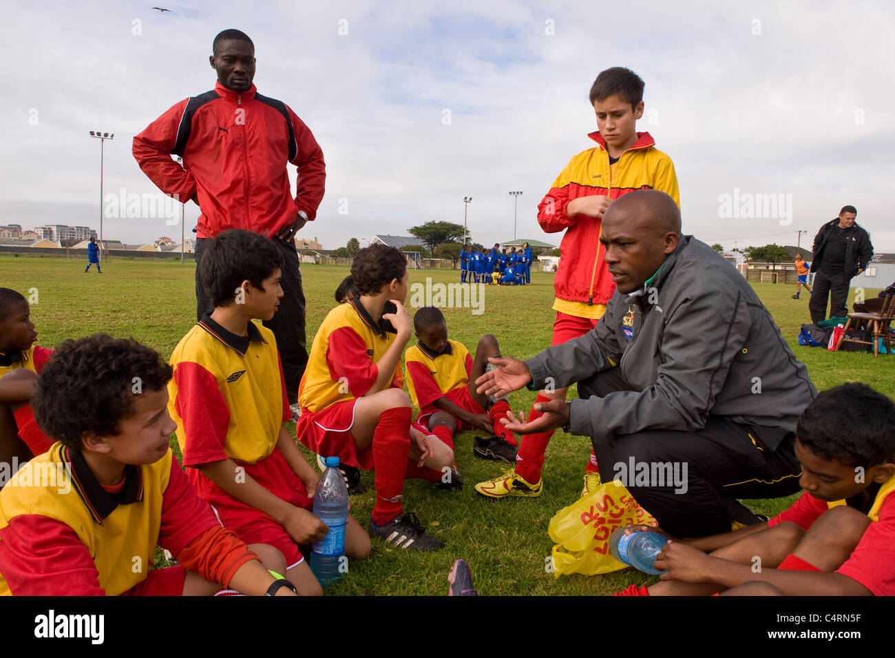 Football coach instructing the Rygersdal Under 13 team during half time Cape Town South Africa - Stock Image