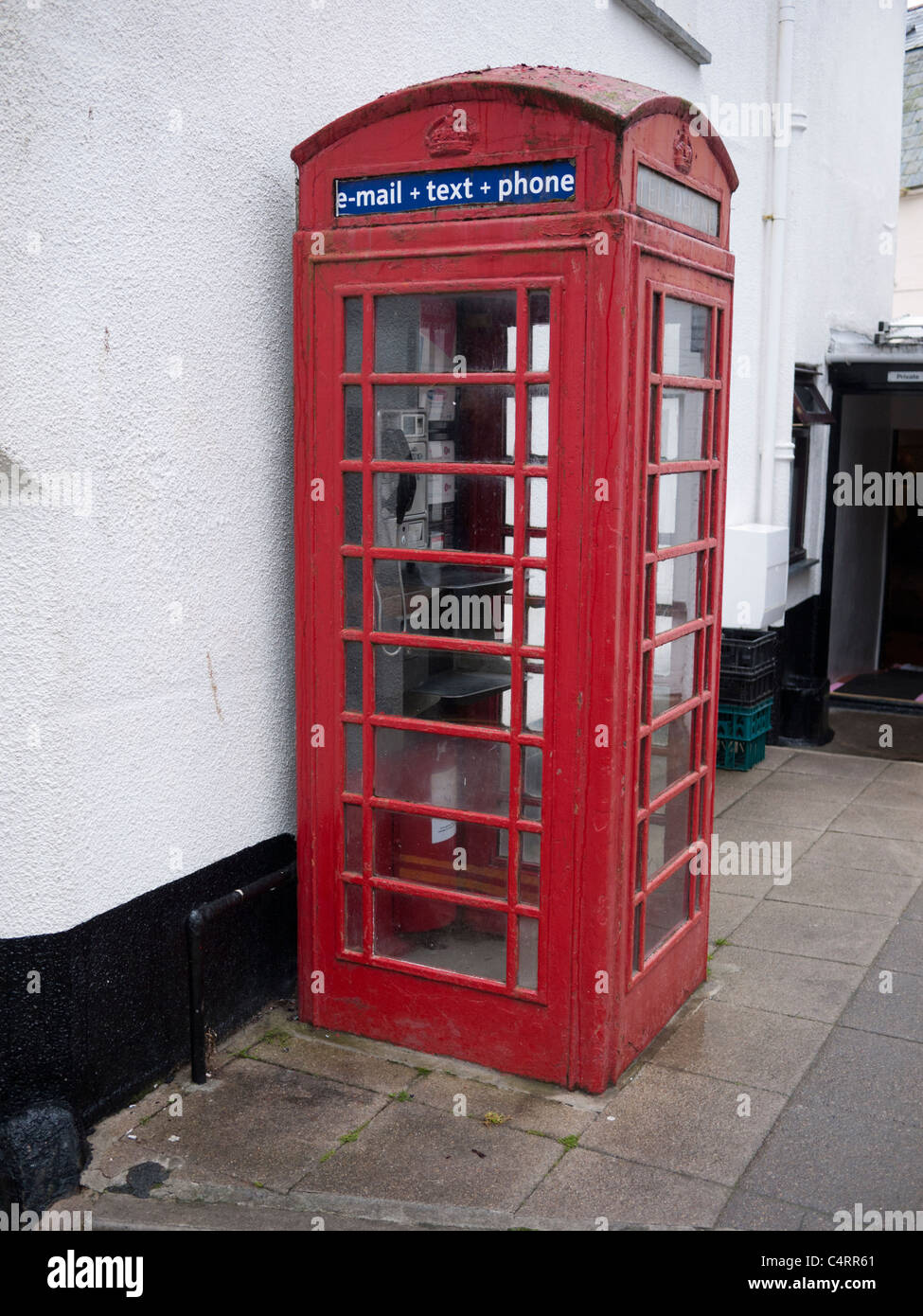 Red traditional English Telephone box in Padstow Cornwall with sign for e mail text and phone - Stock Image