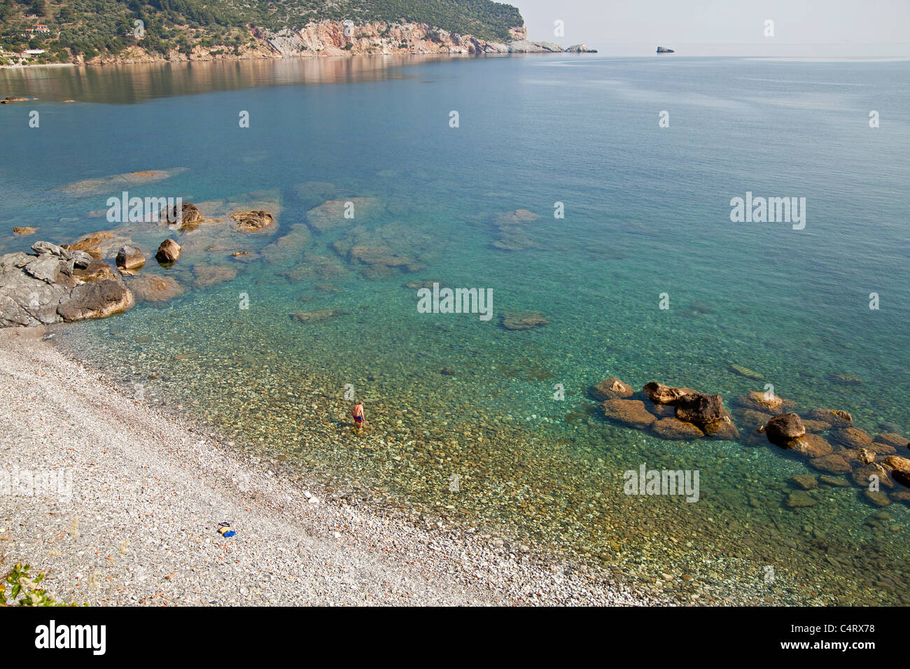 man going swimming at the town beach in Skopelos Town, Skopelos Island, Northern Sporades, Greece - Stock Image