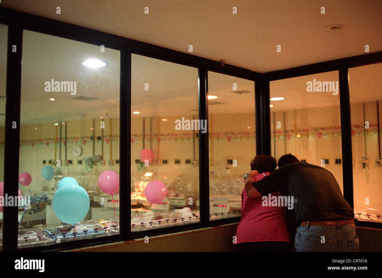 Maternity Nursery Father And Mother Admiring The Newborn Baby Through Glass Window Hospital