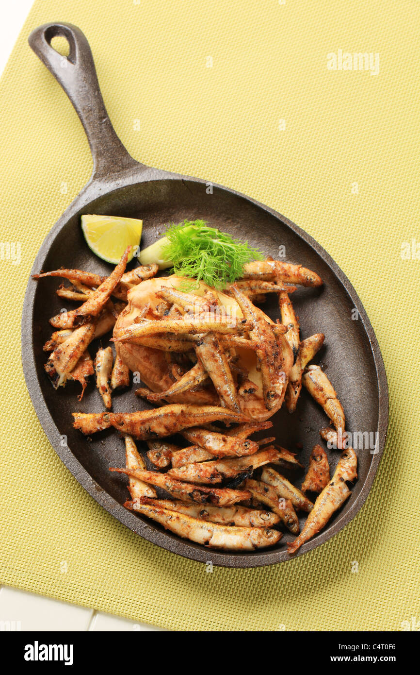 Fried anchovies and baked potato on a frying pan - Stock Image