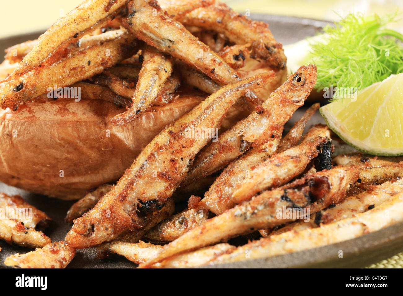 Fried anchovies and baked potato - detail - Stock Image