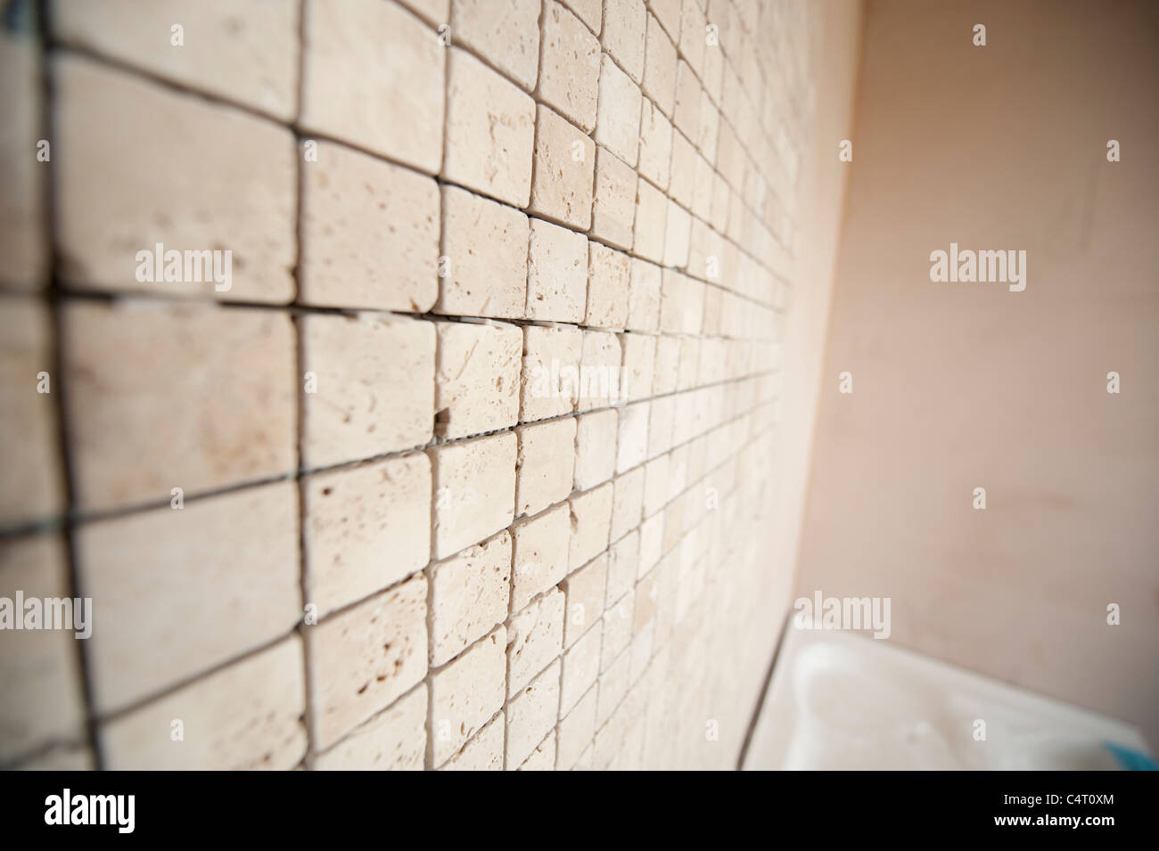 Tiling a bathroom walls with natural Travertine mosaic Stock Photo ...