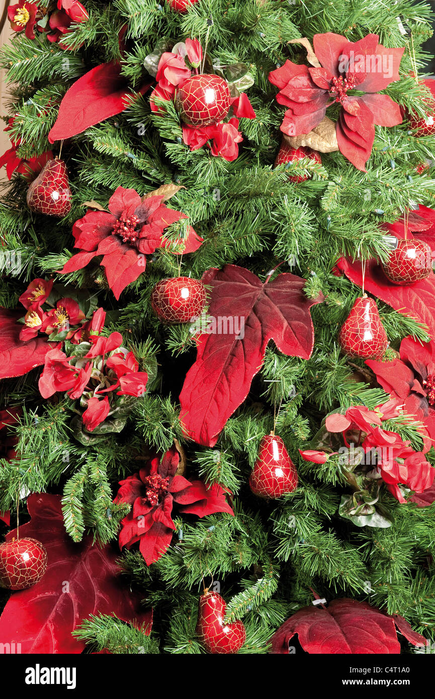 christmas tree decorated with baubles and poinsettia plants holiday green red bauble decorations traditional seasonal