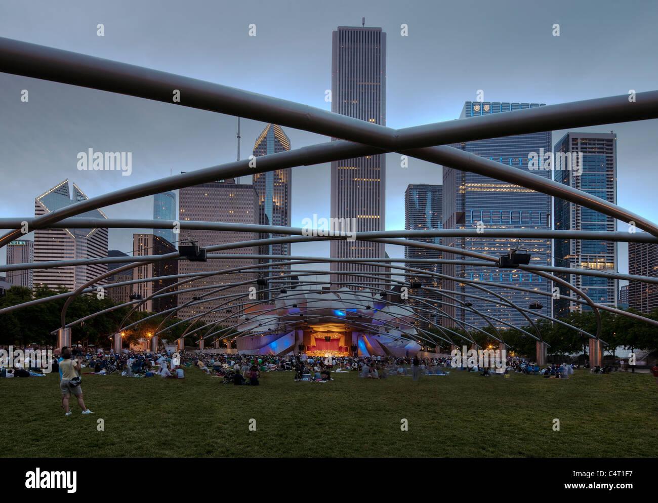 People listen to an evening concert in the Jay Pritzker Pavillion, Millennium Park, Chicago, Illinois. - Stock Image