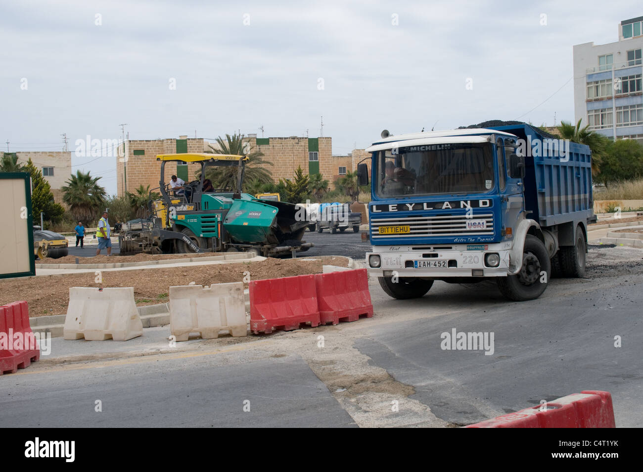 A tarmac laying machine lays a new road surface in preparation of the revised bus station in Bugibba, Malta - Stock Image