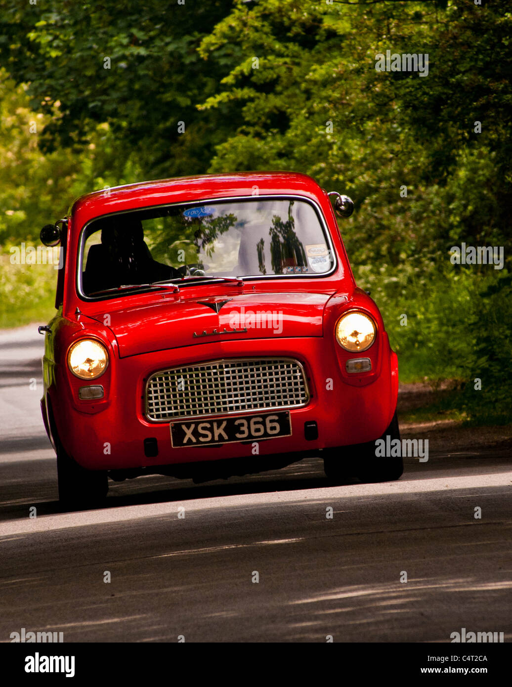 Renovated classic car 1959 Ford Anglia 100E driving in English country lane - Stock Image
