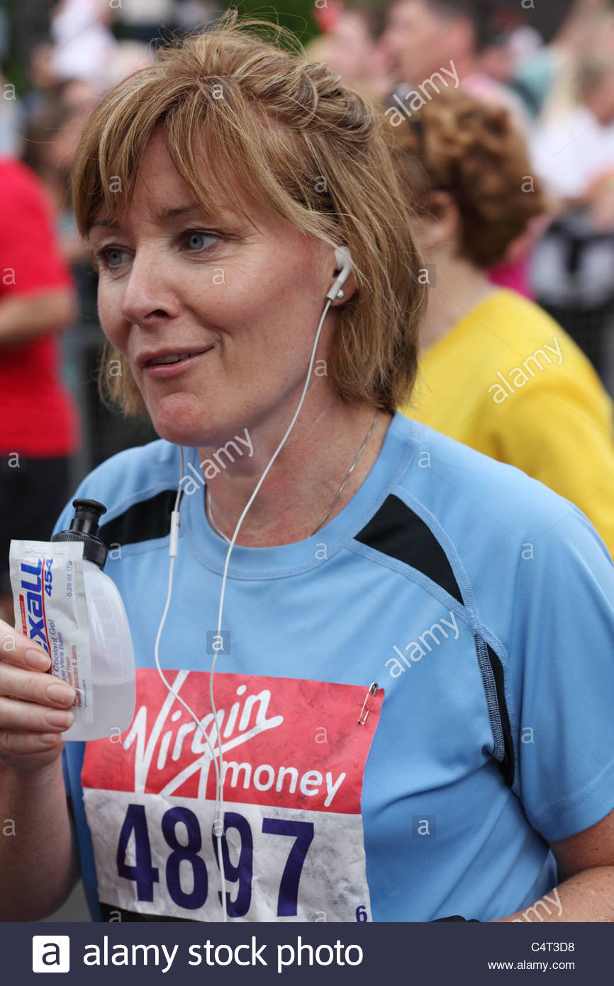 Runner with a drink at the Virgin London marathon - Stock Image