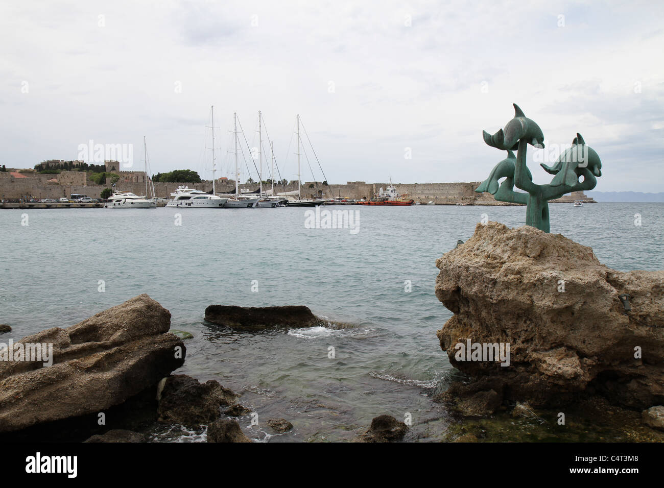 Monument to the dolphins at seaside in Rhodes, Greece. - Stock Image