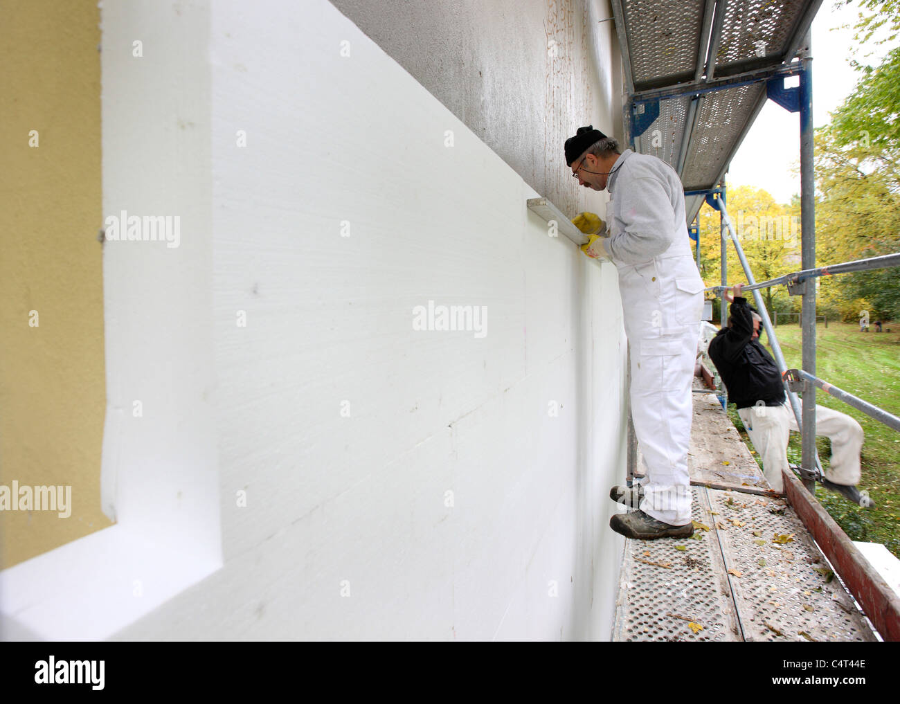 Heat insulation of a building. For saving energy, Styrofoam panels are sticked to the outside wall, to keep the - Stock Image