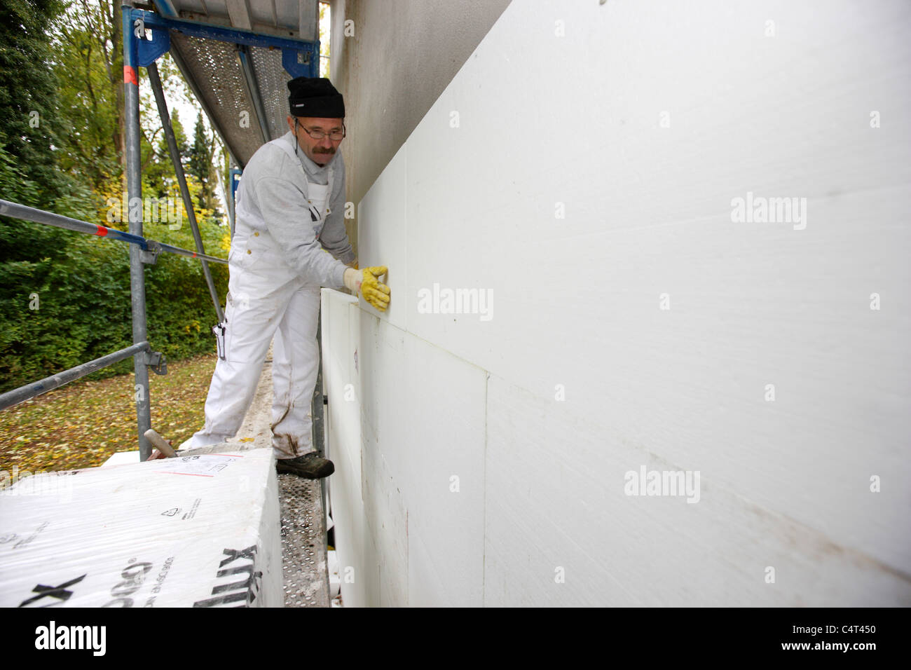 Heat insulation of a building. For saving energy, Styrofoam panels are sticked to the outside wall, to keep the Stock Photo