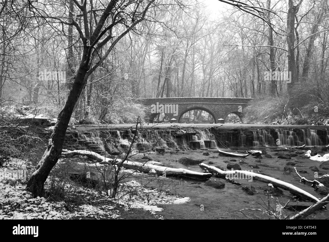 Snow Covered Trees Framing A Stone Bridge And Waterfall During Winter In The Park, Sharon Woods, Southwestern Ohio, Stock Photo