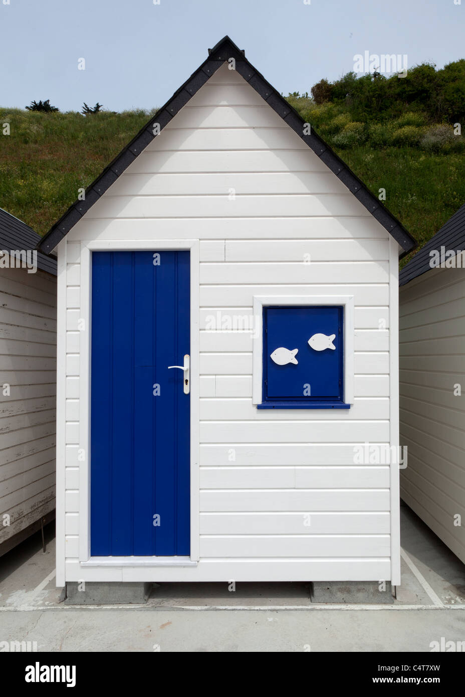 Dare to be different - all the other beach huts are painted white and blue but this one has the dual fish logos. - Stock Image