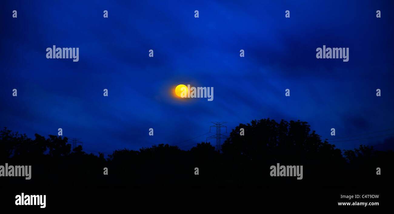 A Yellow Moon On The Rise Against A Deep Blue Twilight Sky And Cloudscape, Southwestern Ohio, USA - Stock Image
