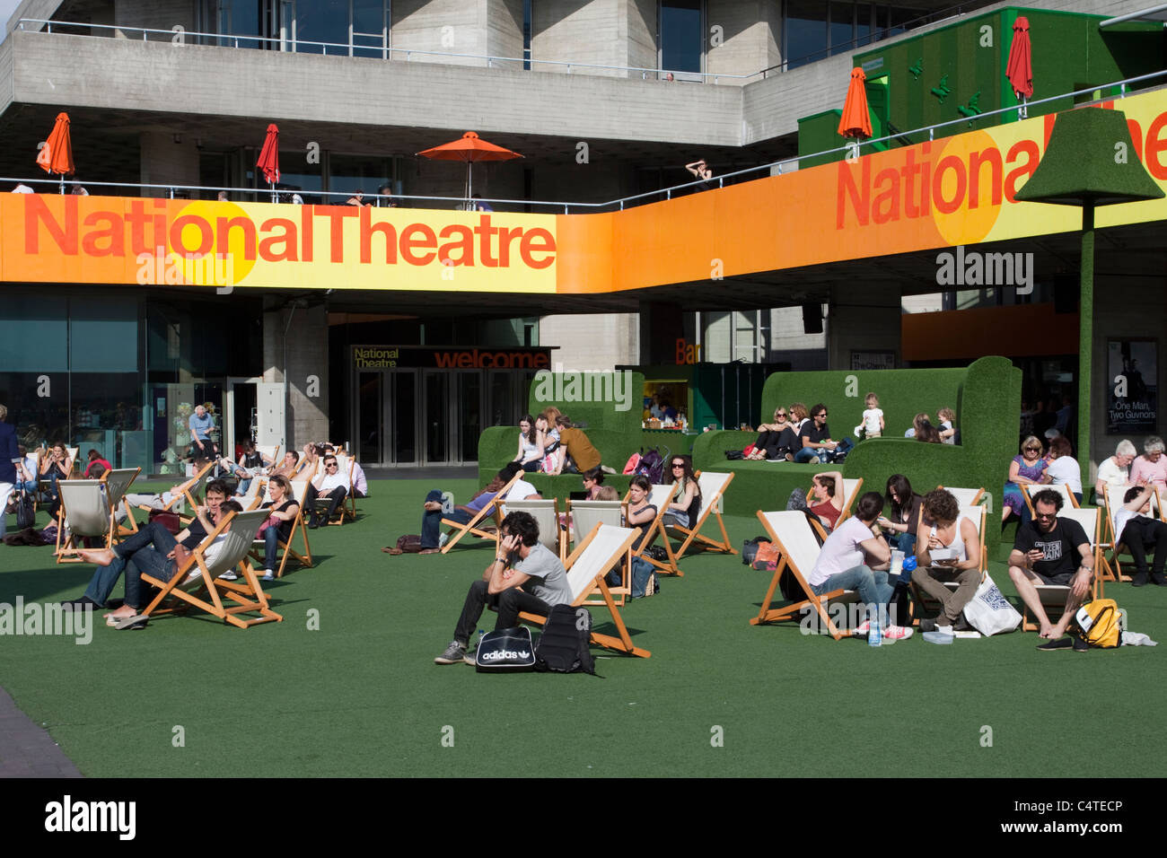 People enjoying the sunshine while sitting on deck chairs outside the National Theatre, South Bank, London, England, - Stock Image