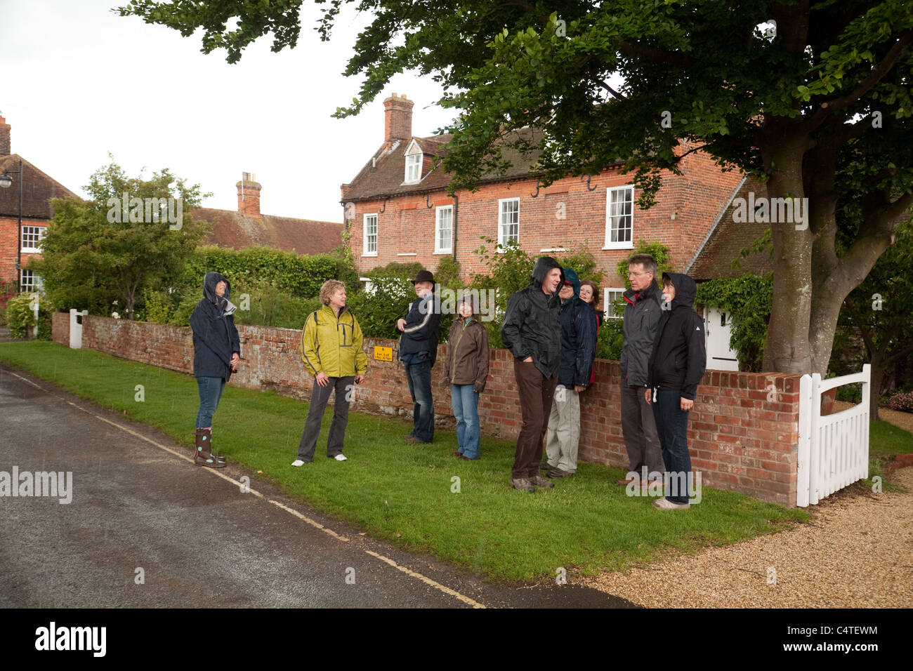 A group of people sheltering under a tree from the rain - Stock Image