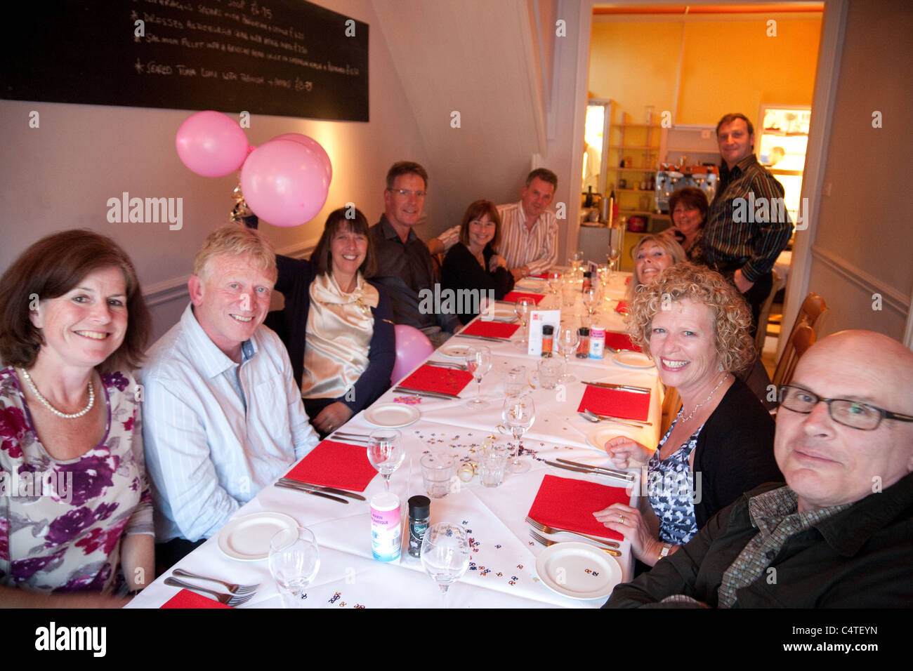 A group of 50 somethings celebrating a 50th birthday in a restaurant, UK - Stock Image