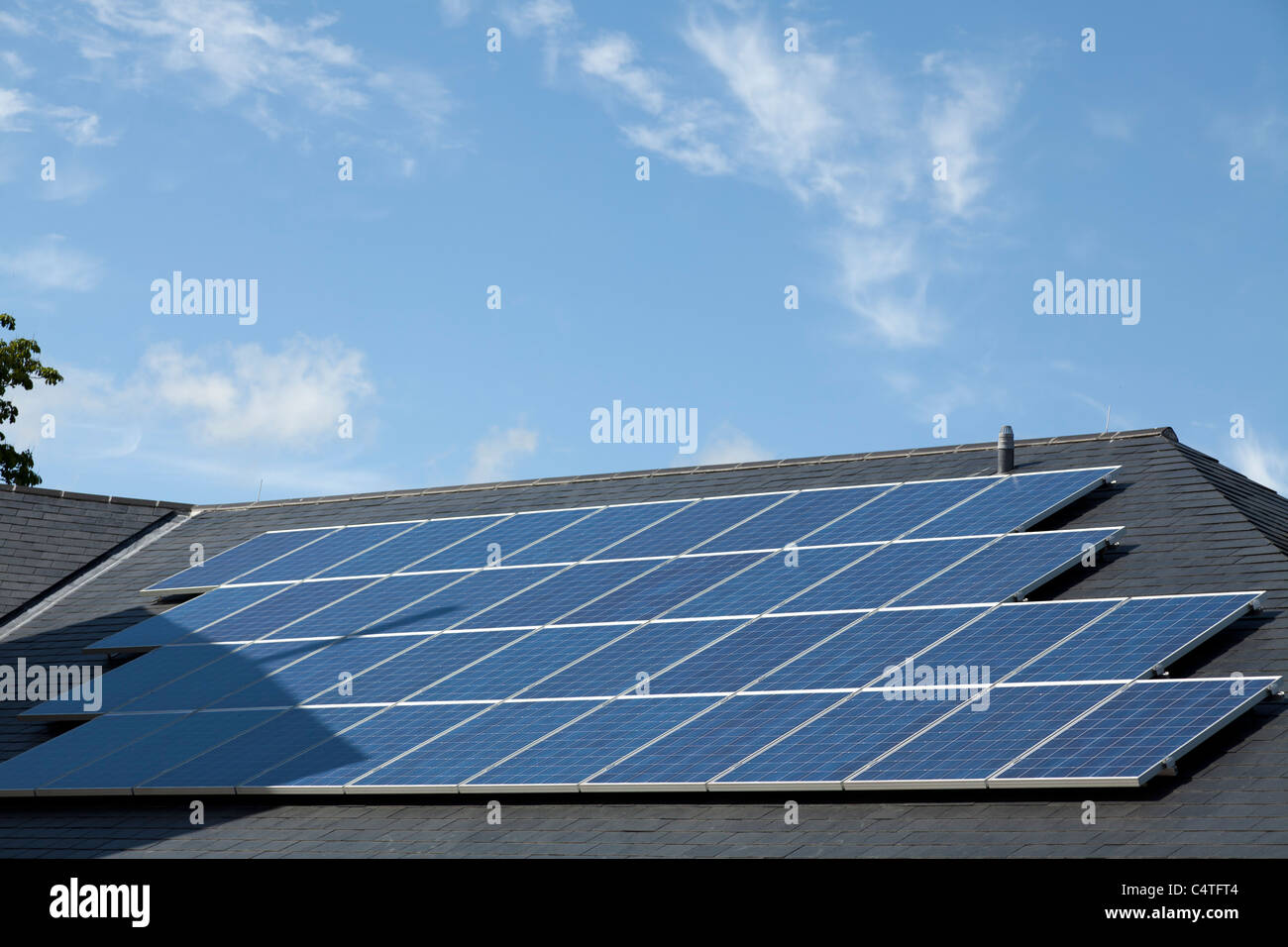 Solar panels on pitched roof  of commercial building - Stock Image