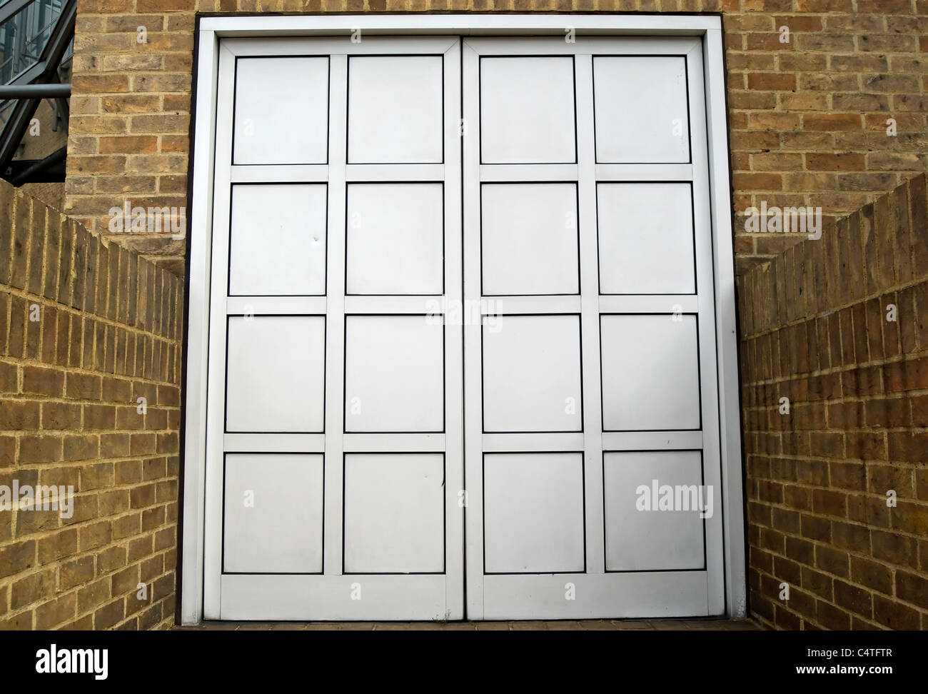 closed double door with no exterior handle set into a brick wall - Stock Image