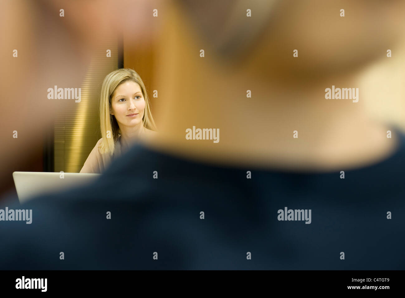 Woman looking away in thought, man in foreground - Stock Image