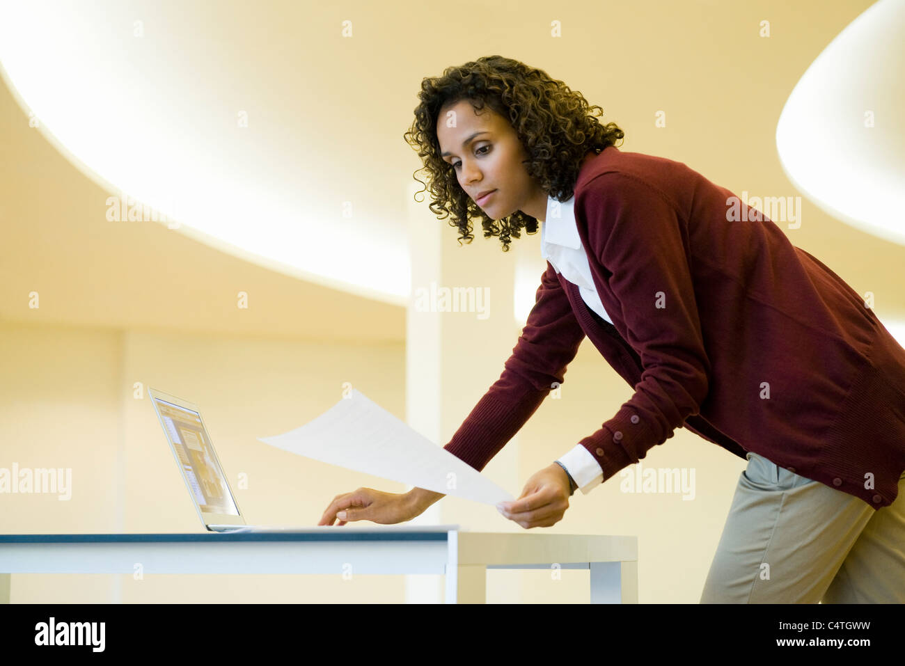 Businesswoman using laptop computer and looking at document - Stock Image