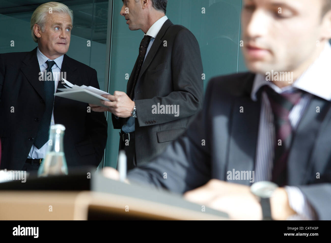 Executive in discussion, young businessman working in foreground - Stock Image