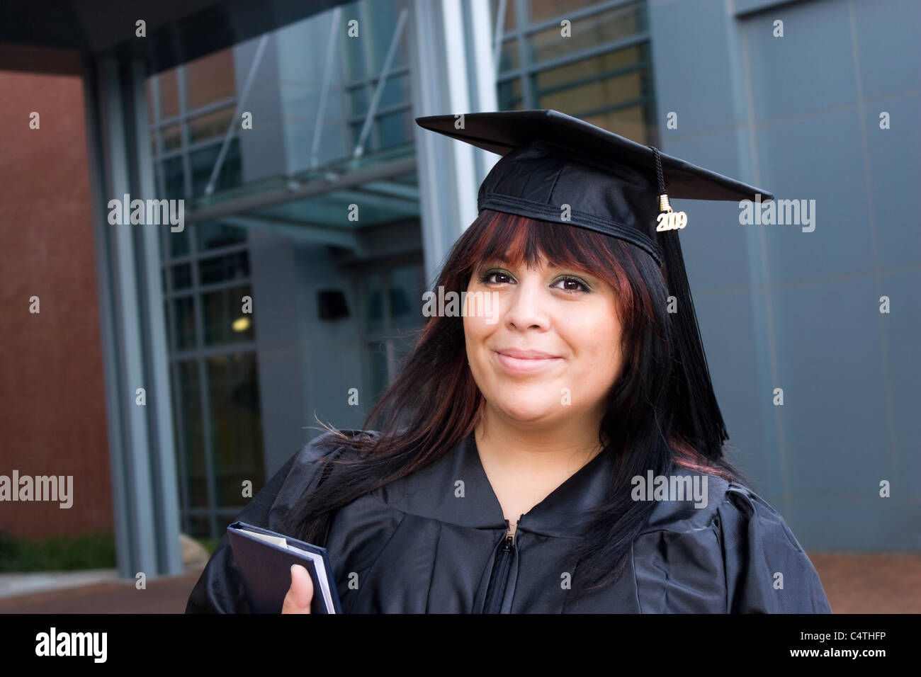 A recent graduate posing in her cap and gown and holding her fresh diploma or degree. Stock Photo