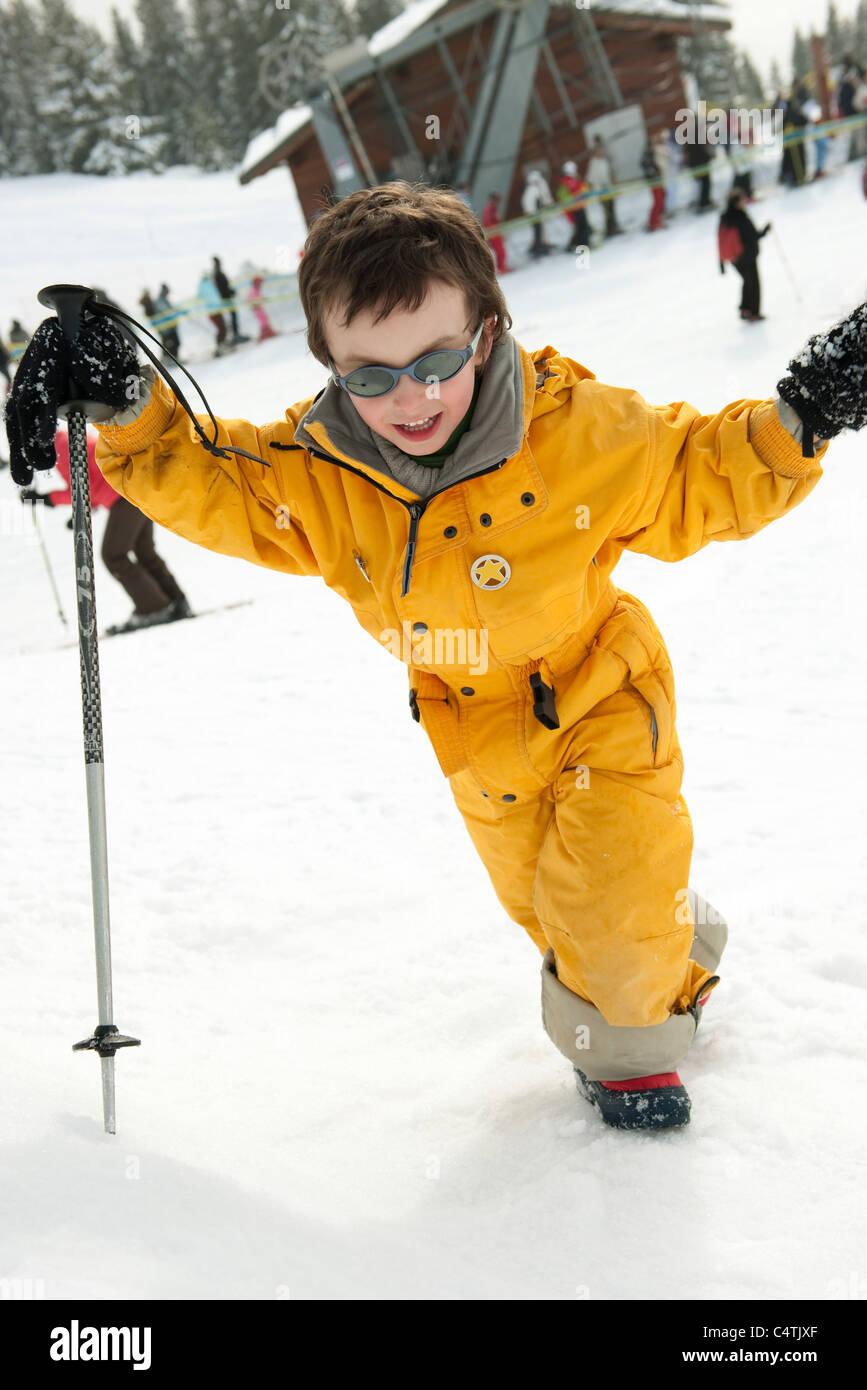 Little boy walking up ski slope - Stock Image
