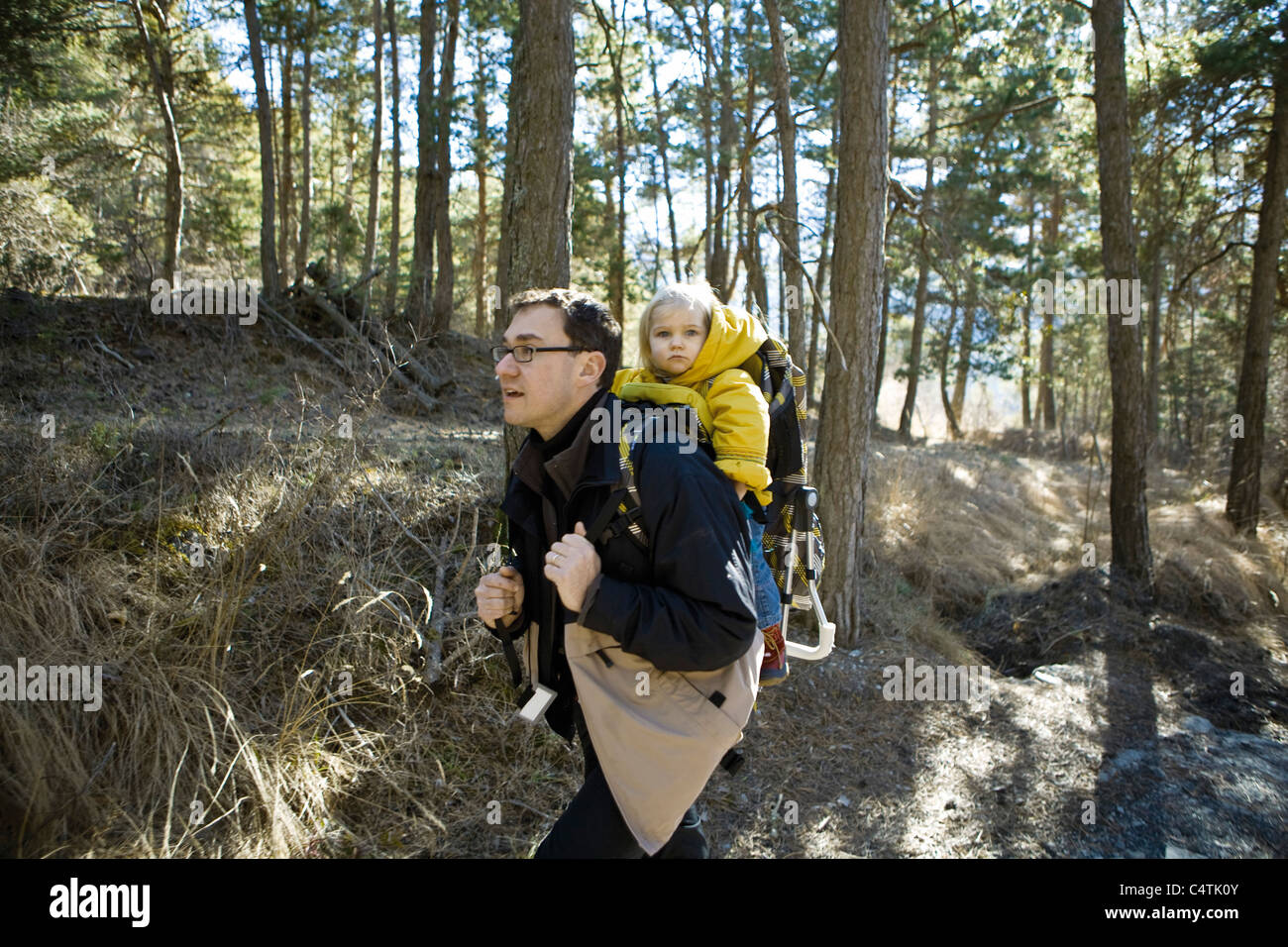 Father hiking in woods with baby daughter in backpack carrier Stock Photo