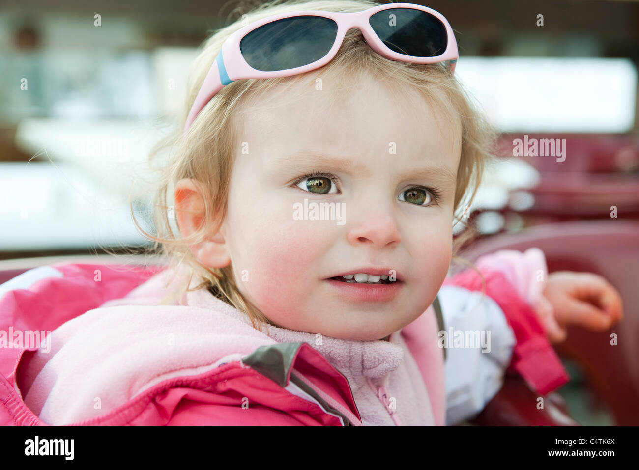 Toddler girl with sunglasses on her head, portrait - Stock Image