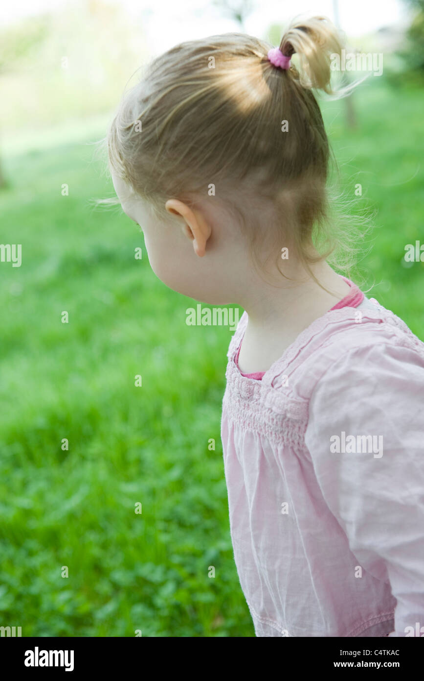Toddler girl outdoors, looking over shoulder - Stock Image