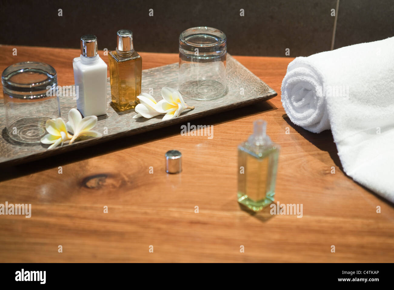 Perfume bottles and frangipani flowers on tray - Stock Image