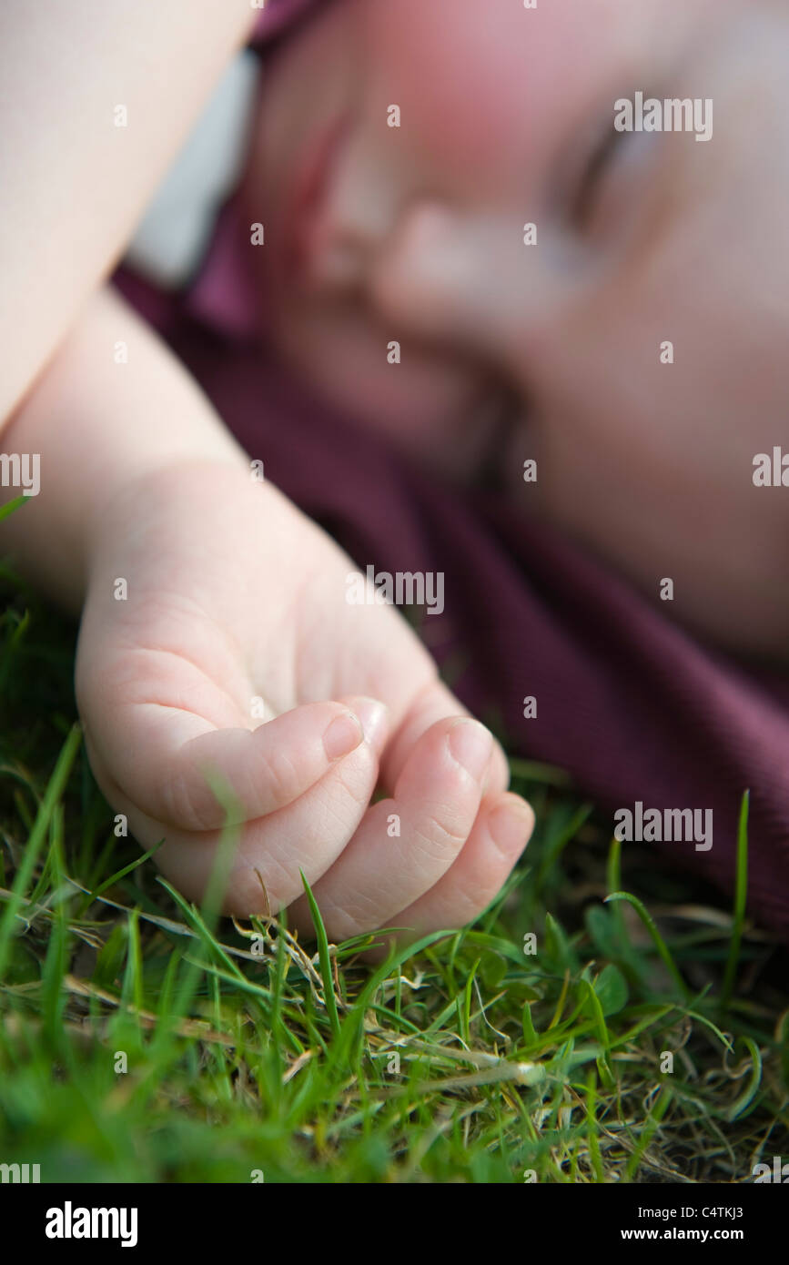 Baby girl napping on grass - Stock Image