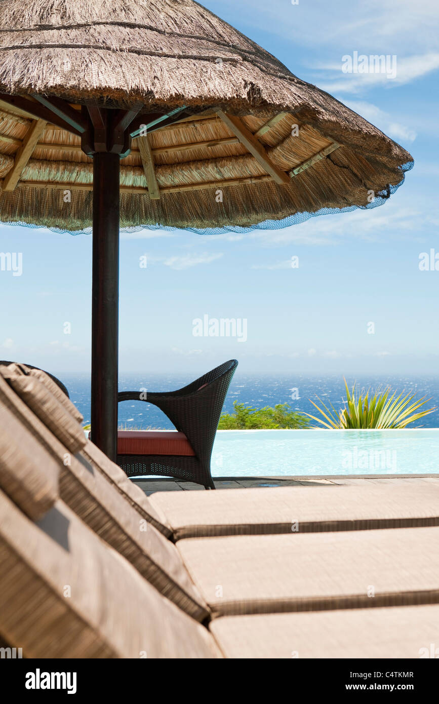 Poolside lounge chairs at seaside resort - Stock Image