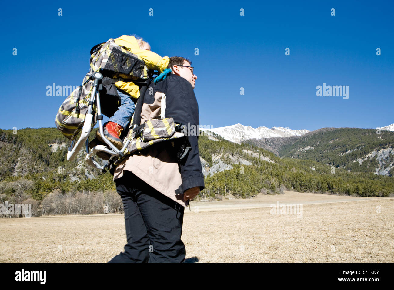 Father hiking with baby in backpack carrier Stock Photo