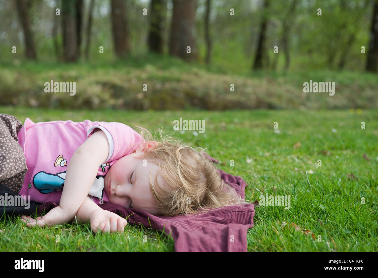 Toddler girl taking a nap outdoors Stock Photo