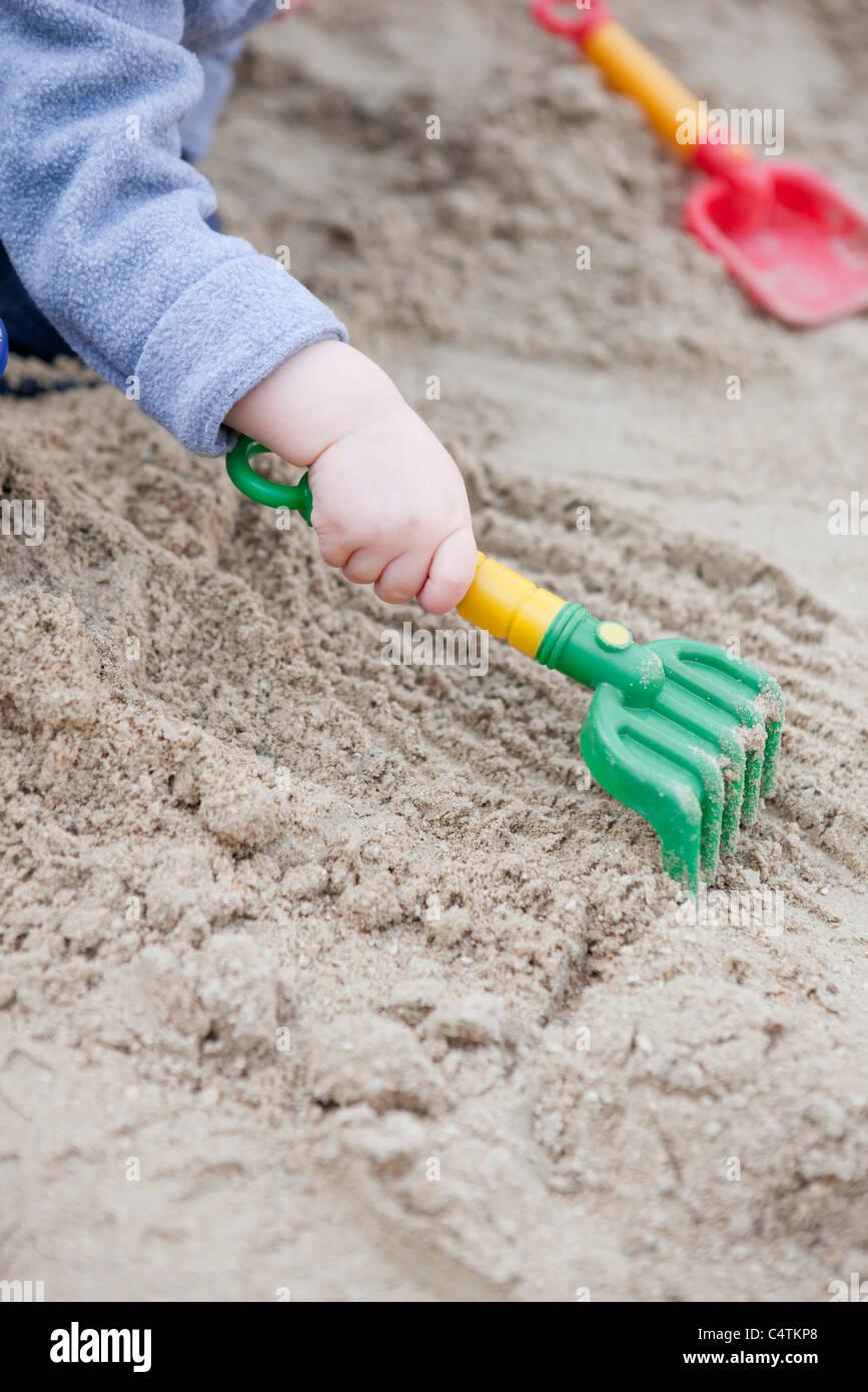 Toddler raking sand, cropped - Stock Image