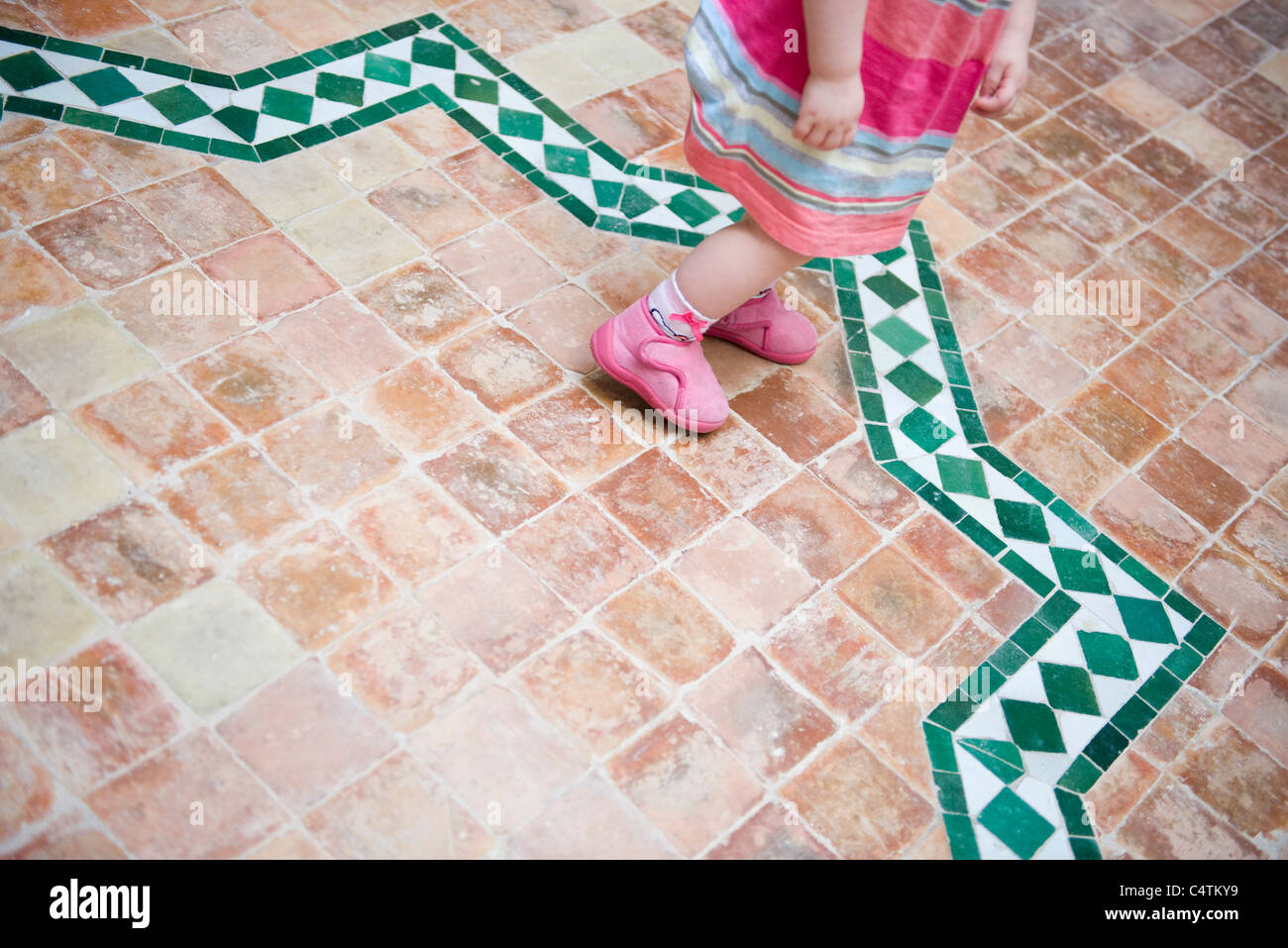 Toddler girl walking on tiled patio, low section - Stock Image